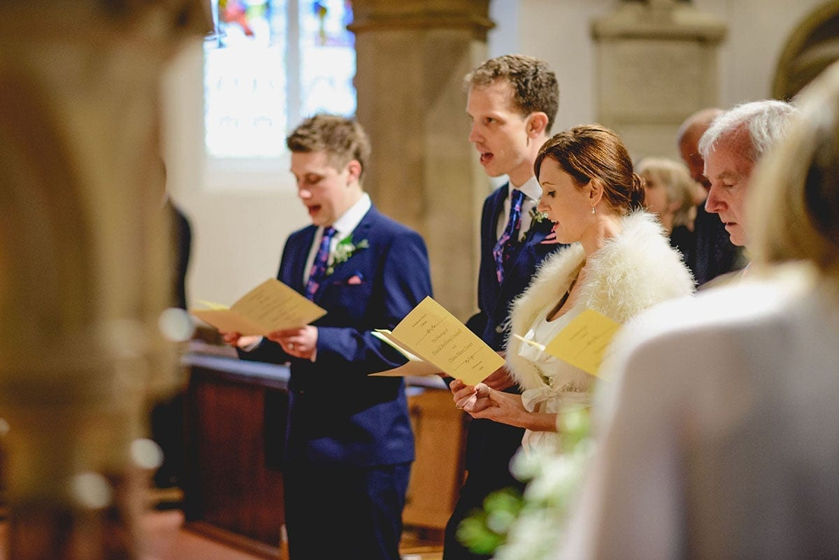Bride and groom sing hymns. Loseley Park Wedding Photographer