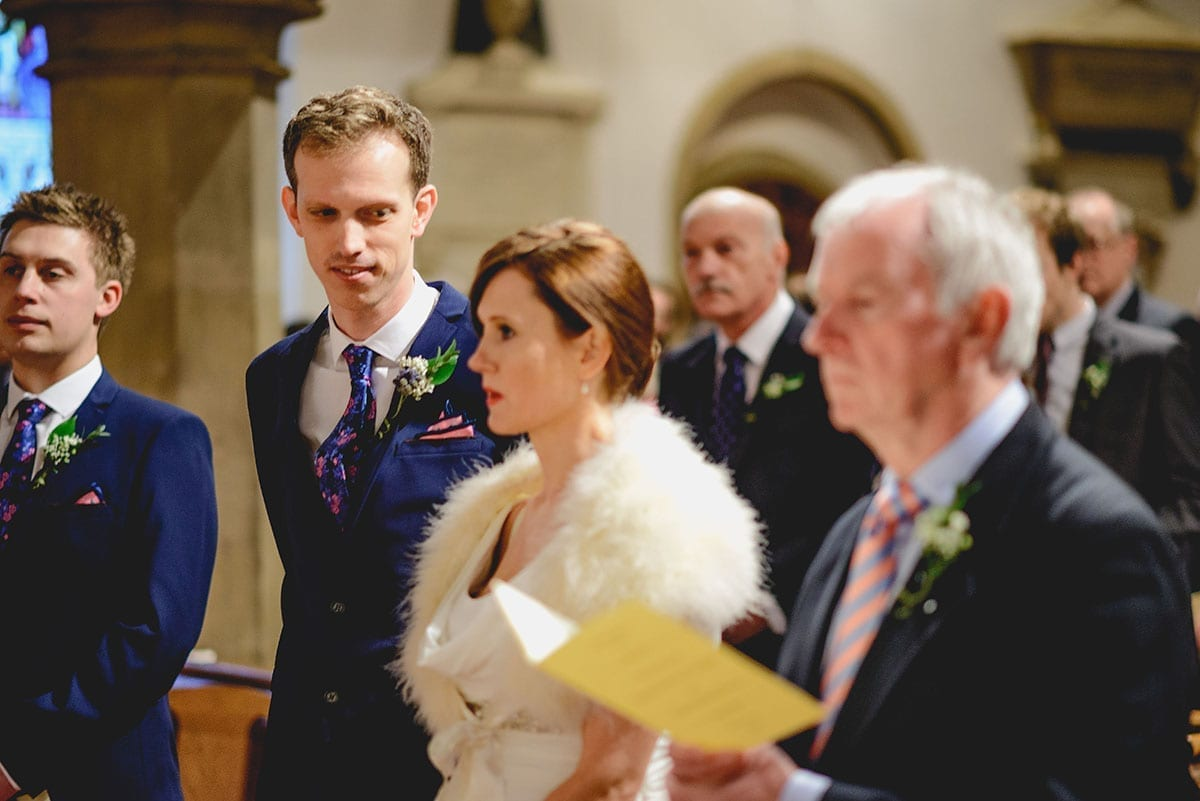 Groom looks at his stunning bride at the church. Loseley Park Wedding Photographer