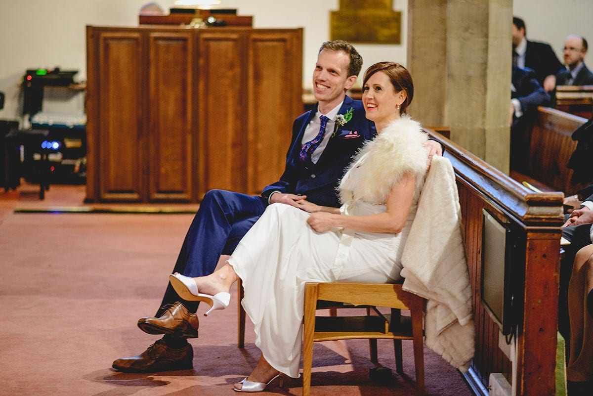 Bride and groom listen to reading at church. Loseley Park Wedding Photographer